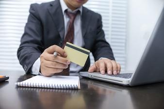 クレジットカードを持ってラップトップコンピュータを使用している実業家。オンラインショッピングのコンセプト。