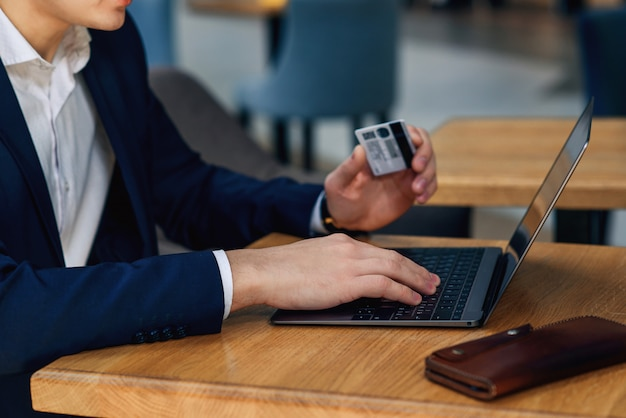 Businessman holding credit card typing numbers on computer keyboard while sitting at cafe at the wooden table