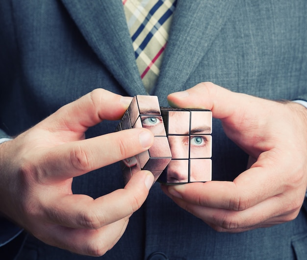 Бизнесмен, держа в руках куб