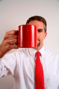 Businessman holding cup, close-up