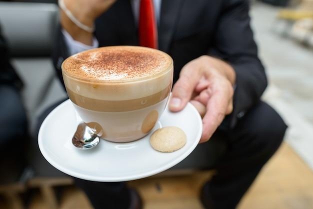 Бизнесмен, держащий чашку капучино с шоколадом, посыпает пеной и печеньем сбоку
