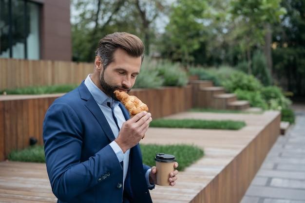 Бизнесмен, держа чашку кофе, едят круассан на улице концепция обеденного перерыва на кофе