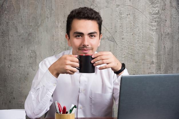 Бизнесмен, держа чашку чая за офисным столом.