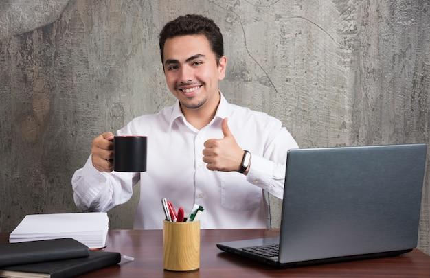 Uomo d'affari che tiene tazza di tè e mostra i pollici in su alla scrivania in ufficio.