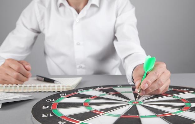 Businessman holding dart arrow in target dartboard