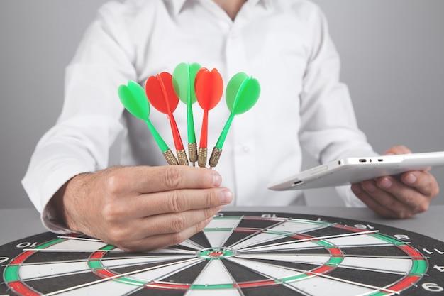 Businessman holding dart arrows in target dartboard.
