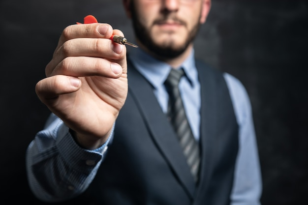 Businessman holding a dart on a black surface