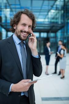 Бизнесмен, проведение цифровой планшет, разговор по мобильному телефону