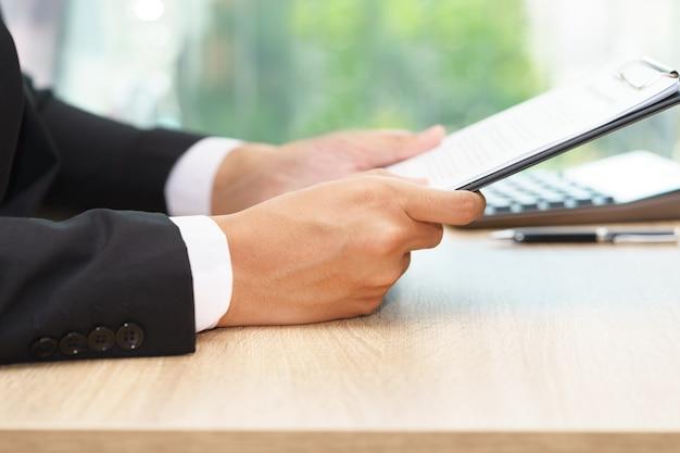 木製の机の上に計算機で文書を保持している実業家。