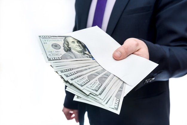 Businessman holding dollar banknotes and envelope in hands