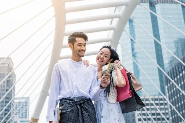 ノートパソコンでドルの現金を保持している実業家と買い物袋を保持しているアジアの女性は、都市で幸せな笑顔