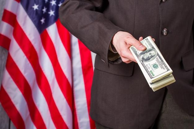 Бизнесмен, держащий доллары рядом с флагом. флаг сша, человек и деньги. наша страна - наши правила. предлагаю вам присоединиться к нам.