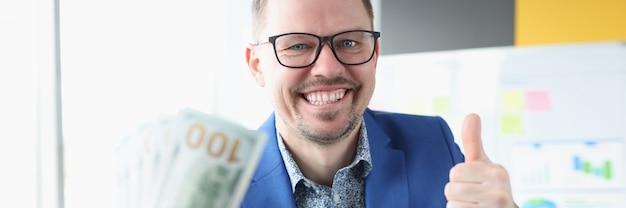 Бизнесмен держит доллары в руках и показывает большой палец вверх успешной работы в интернете