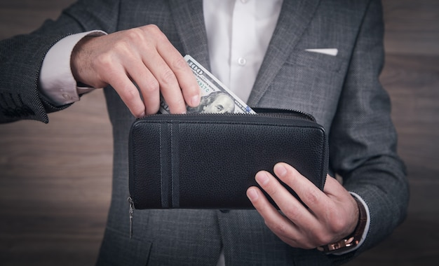 Businessman holding dollars with wallet.