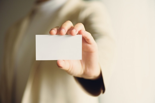Businessman holding empty business card with copy space.