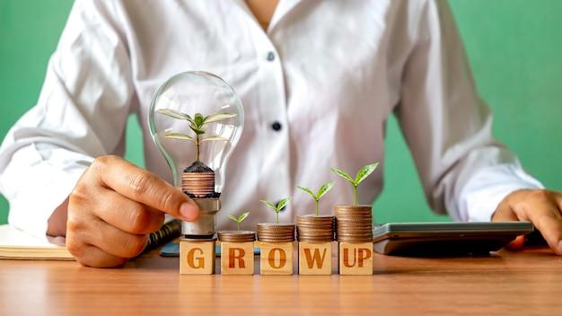 Бизнесмен, держащий энергосберегающие лампы с растениями, растущими на монетах, и деревьями, растущими на монетах, идеями для открытия бизнеса и финансовым ростом.