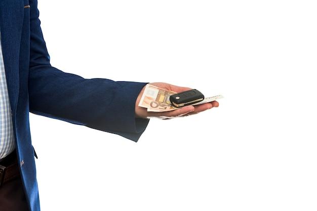 白い壁のクローズアップで分離されたユーロ紙幣と車の鍵を保持しているビジネスマン。車のコンセプトを購入またはレンタルする