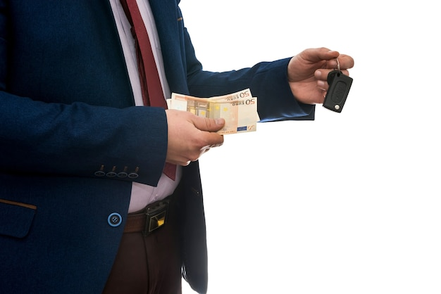 Businessman holding euro banknotes and car keys isolated. buy or rent car concept