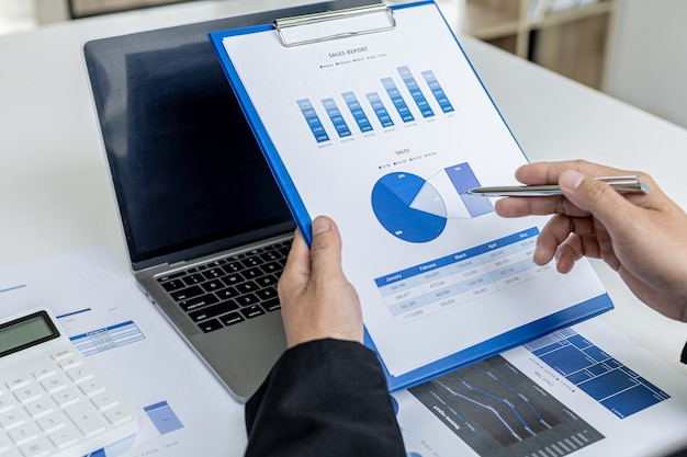 Бизнесмен, держащий финансовые документы, он владеет компанией, он проверяет финансовые документы компании в офисе, финансовые документы показывают формат диаграммы. понятие финансового менеджмента.