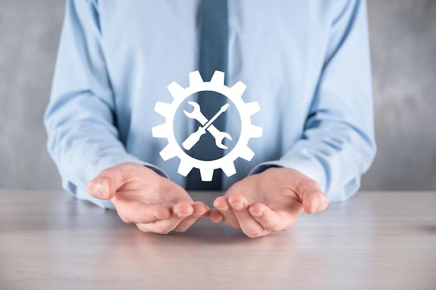 Бизнесмен, держа значок шестеренки с инструментами. приспособление. концепция целевой фокус цифровой диаграммы, графических интерфейсов, виртуального экрана пользовательского интерфейса, сетевых подключений