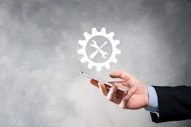 도구와 기어 아이콘을 들고 사업가 대상 초점 디지털 다이어그램, 그래프 인터페이스, 가상 ui 화면, 연결 netwoork의 gearing.concept