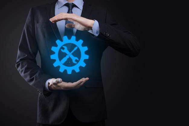 Бизнесмен, держа значок шестеренки с инструментами. приспособление. концепция целевой фокус цифровой диаграммы, графических интерфейсов, виртуального экрана пользовательского интерфейса, сетевых подключений.