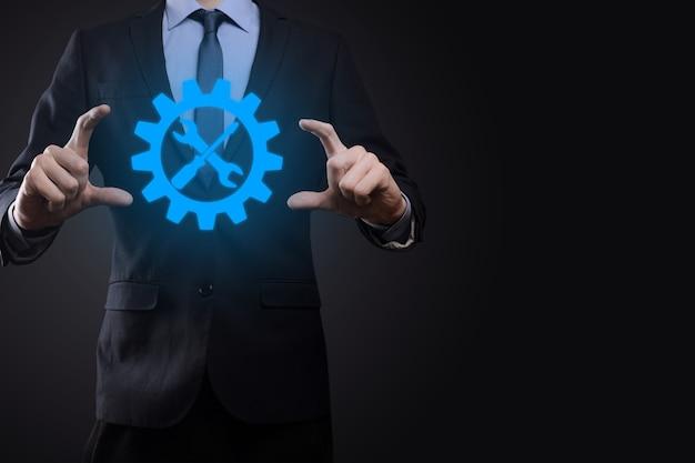 Бизнесмен, держащий символ шестерни с инструментами. приспособление. концепция целевой фокус цифровой диаграммы, графических интерфейсов, виртуального экрана пользовательского интерфейса, сетевых подключений.