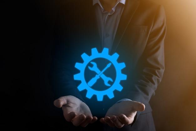 도구와 기어 기호를 들고 사업가 대상 초점 디지털 다이어그램, 그래프 인터페이스, 가상 ui 화면, 연결 netwoork의 gearing.concept.