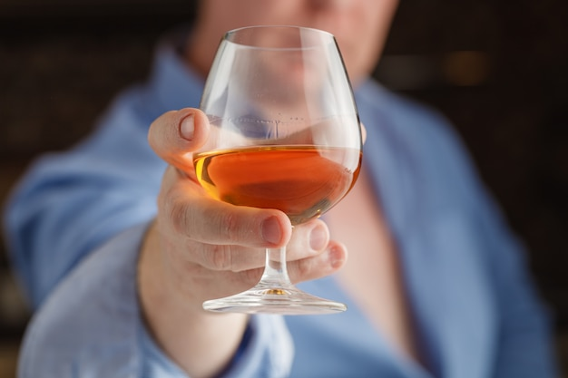 Businessman holding a glass of whisky, close up