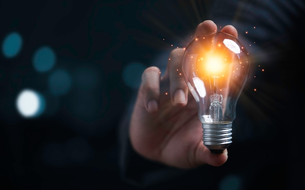 Businessman holding glowing light bulb for creative thinking ideas and innovation concept.
