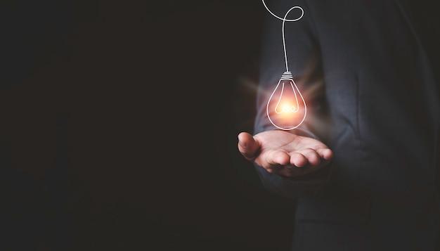 Бизнесмен, держащий светящуюся лампочку и использующий компьютерный ноутбук для ввода идеи бизнес-стратегии, идей творческого мышления и концепции инноваций.
