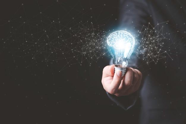Бизнесмен, держащий светящуюся лампочку с рисунком мозга и линии связи, творческими идеями мышления и инновационной концепцией.