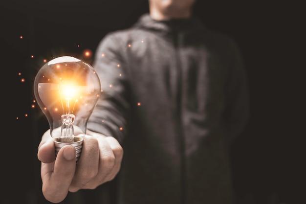 오렌지 빛으로 빛나는 전구를 들고 사업가입니다. 창의적인 새로운 사업 아이디어 개념입니다.
