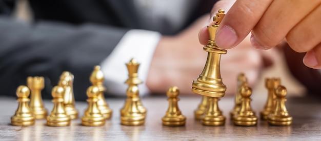 Бизнесмен, держащий фигуру золотой шахматный король.