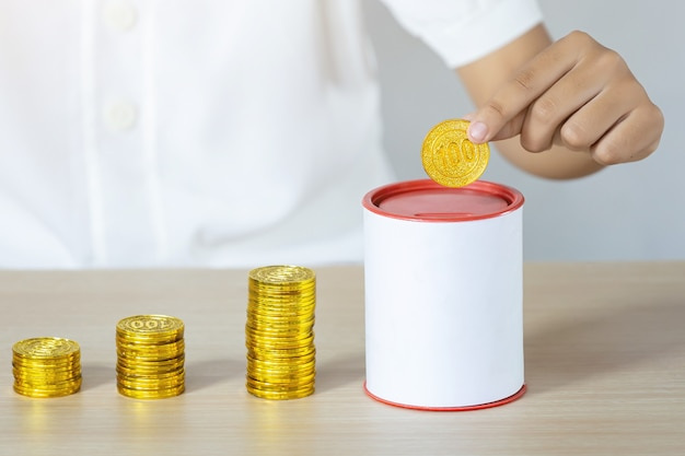 Businessman holding gold coins putting in coin bank. concept saving money for finance accounting