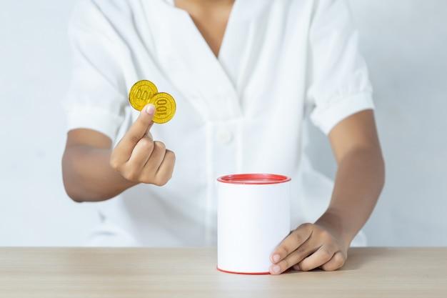 貯金箱に入れて金貨を保持しているビジネスマン。財務会計のためのお金を節約する概念