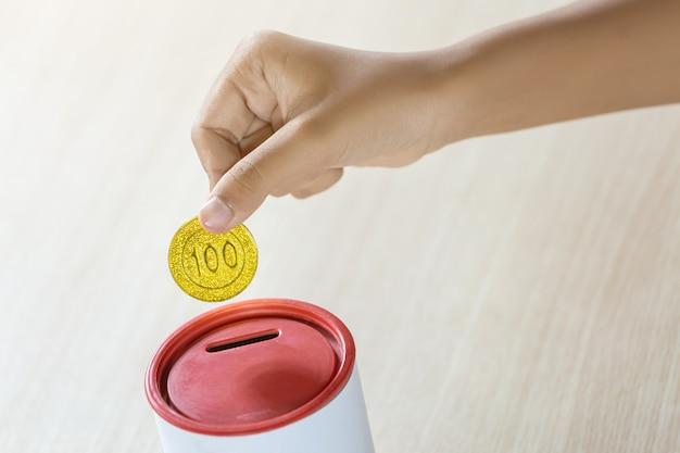 Бизнесмен держа золотые монетки кладя в банк монетки