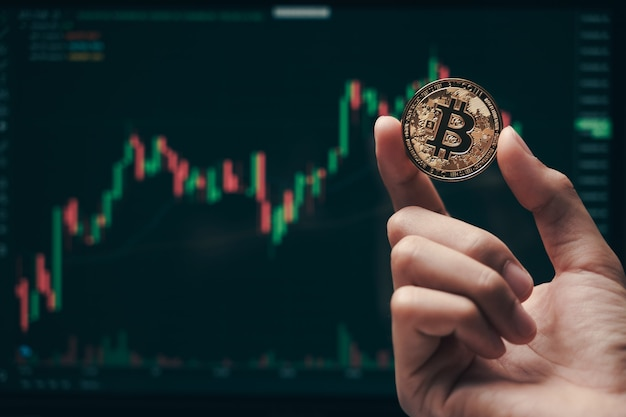 Businessman holding golden bitcoin on computer trading chart screen background. stock, cryptocurrency trading concept.