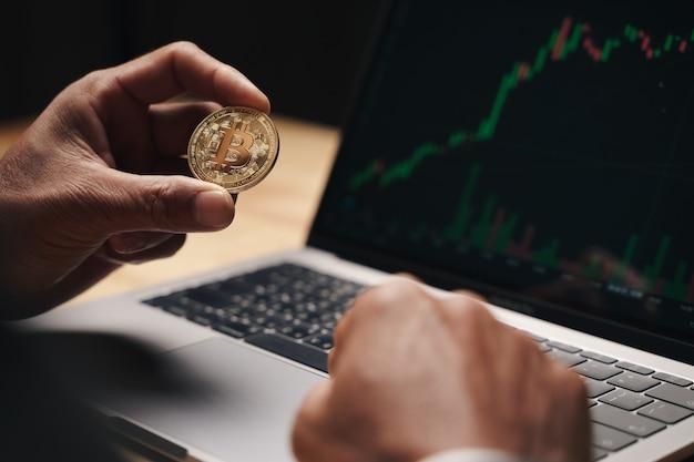 Бизнесмен, держащий золотой биткойн на фоне экрана компьютерной торговой диаграммы. акции, концепция торговли криптовалютой.