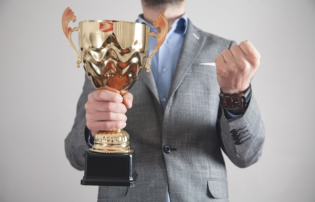 Businessman holding golden trophy. business, success