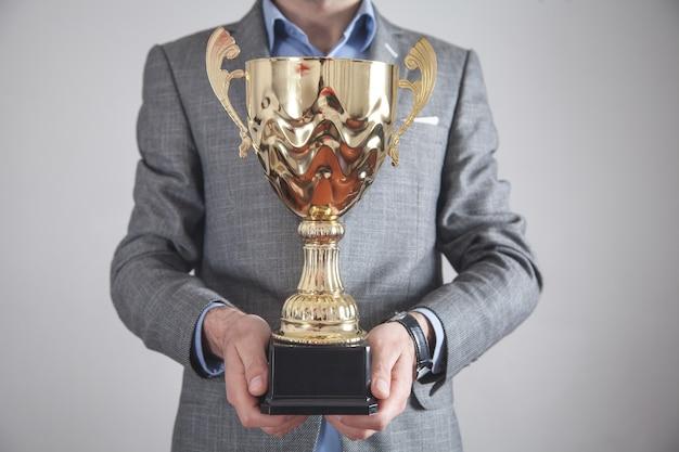 Businessman holding golden trophy. business, success