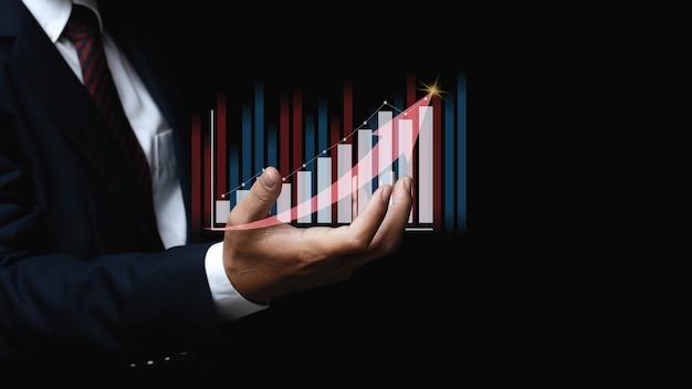グラフ財務チャートを保持しているビジネスマン。デジタルビジネスホログラムグラフ財務チャートの背景。ビジネスと金融の概念のために。