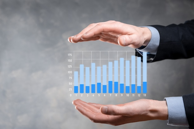 사업가 그래프 성장 및 그의 비즈니스에서 차트 긍정적 인 지표의 증가를 유지합니다. 영업 데이터 및 경제, 전략 및 계획, 디지털 마케팅 및 주식 분석 개념. 투자
