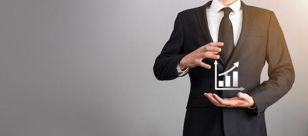 비즈니스에서 그래프 성장 및 차트 긍정적 지표의 증가를 들고 있는 사업가