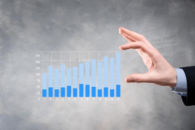 彼のビジネスでグラフの成長とチャートの肯定的な指標の増加を保持しているビジネスマン