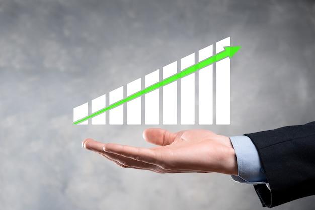 グラフの成長とチャートの肯定的な指標の増加を保持しているビジネスマン。