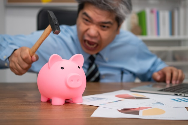 ハンマーを持っているビジネスマンと貯金箱を壊しています