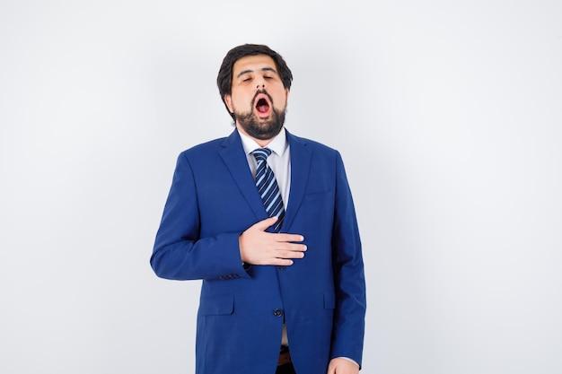 ジャケットに手を握り、フォーマルなスーツであくびをし、眠そうに見えるビジネスマン。正面図。 無料写真