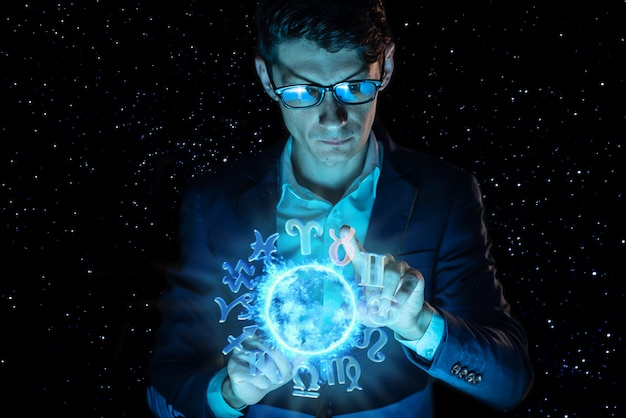 Businessman holding hands over the magic sphere with a horoscope to predict the future. astrology as a business