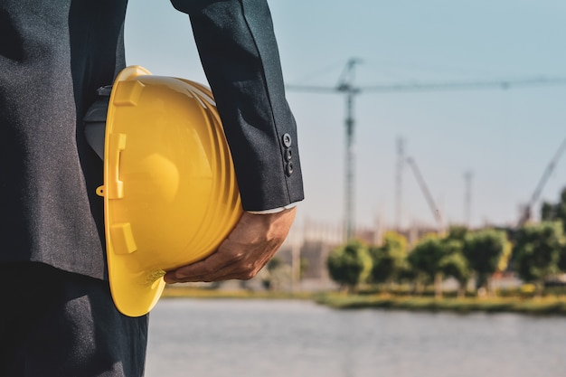 Businessman holding hard hat on site construction